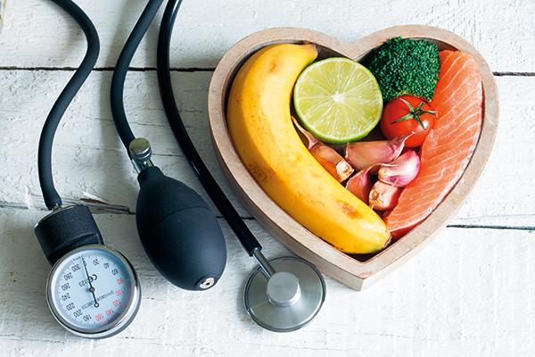 혈압 측정기와 하트모양 보울에 담긴 연어와 채소